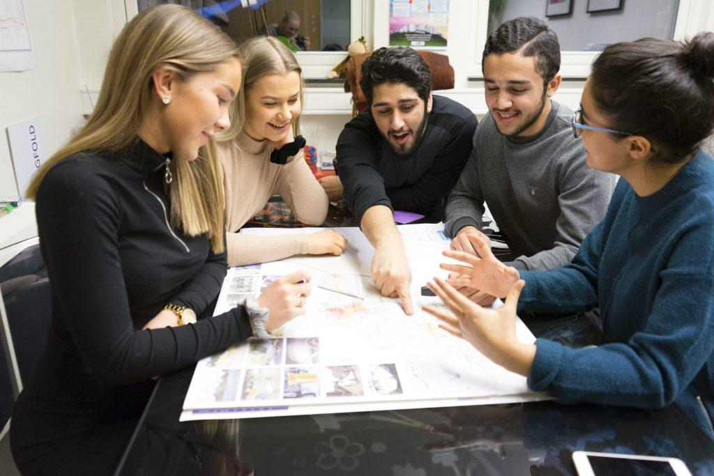 Fem ungdommer sitter rundt et bord og snakker om planer for parken