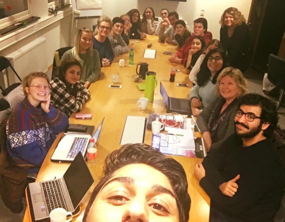 En ungdom ca 15 år tar en selfie. I bakgrunnen er et møtebord med 18 personer rundt, både ungdom og voksne
