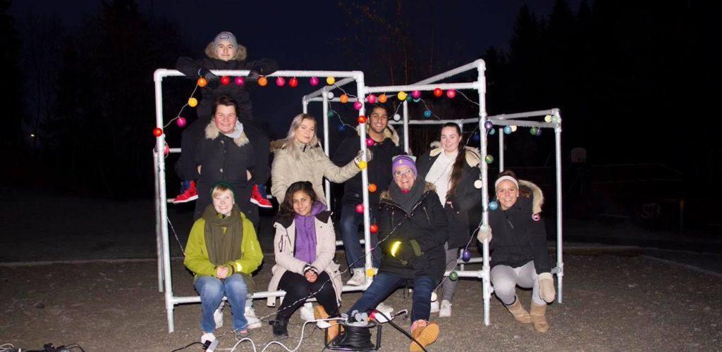 Barn og unge samlet rundt et lyssatt leikestativ.