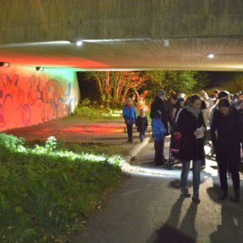 Ei folkemengde betrakter røde og grønne lys på veggen i en fotgjengerundergang