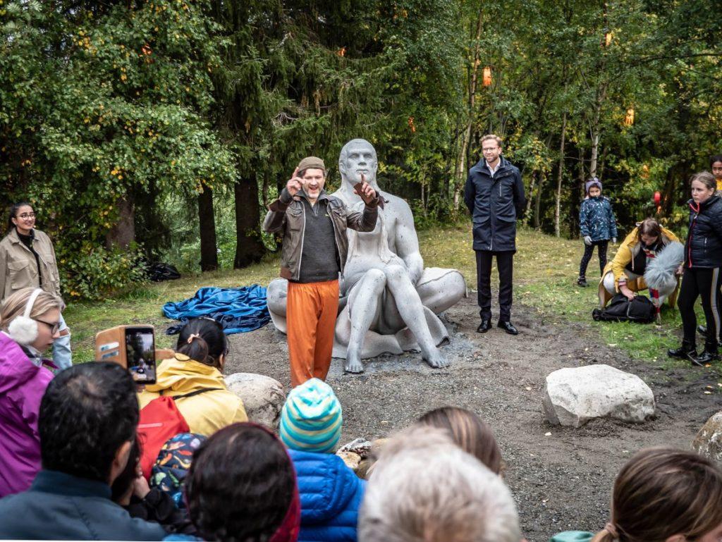 En blid kunstner holder en uformell tale foran ei lita folkemengde.