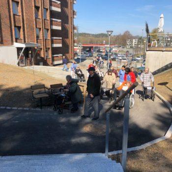 Eldre med rullator og i rullestol beveger seg oppover en nyanlagt gangvei mellom høye blokker i vårsola