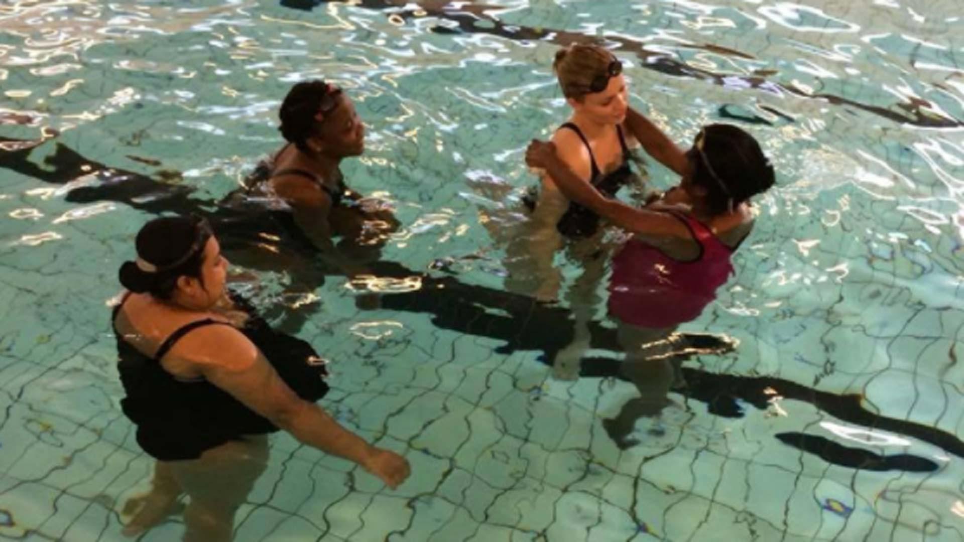 Fire kvinner i et basseng øver på å flyte på ryggen