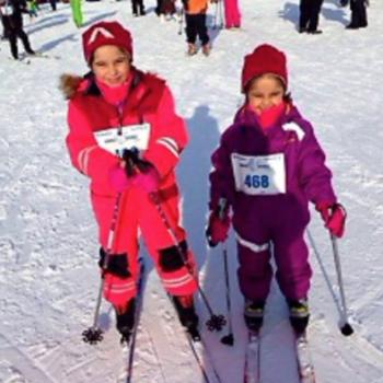 To blide jenter ca 6-8 år på ski med nummerlapp foran på parkdressene