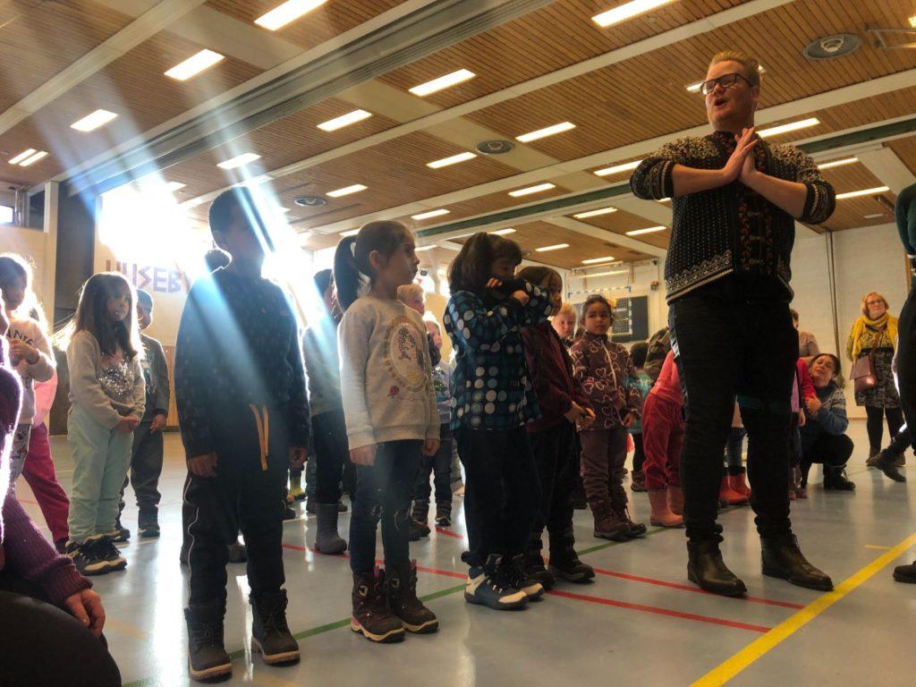 Barnehagebarn som skal synge på konsert ser forventningsfullt opp på en sangpedagog som er dirigent.
