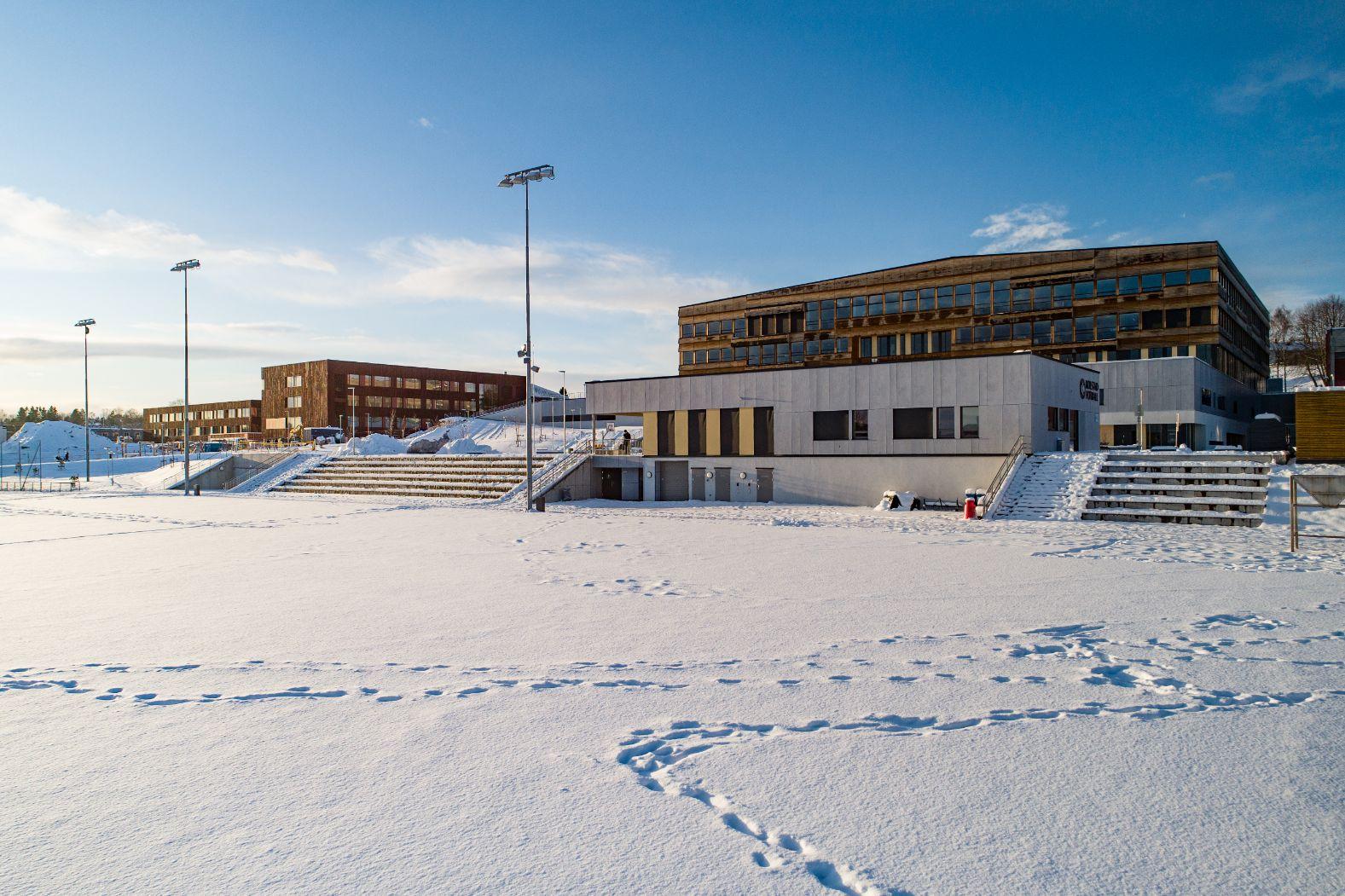 Klubbhus ved snødekt fotballbane. Skolebygg i bakgrunnen
