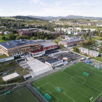 Dronebilde av skoleanlegg med idrettspark i forgrunnen. Bydel og skog i bakgrunnen.