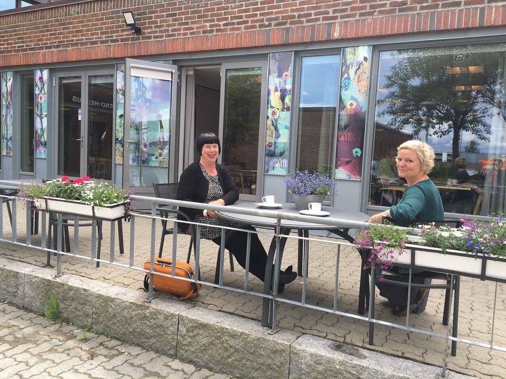 To damer sitter ved et bord utenfor en kafé