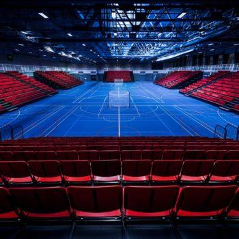 Interiør fra stor og moderne idrettshall, tribuner er trukket ut