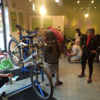 Folk i sykkelantrekk står og ser på at en mekaniker fikser en sykkel som står opp ned
