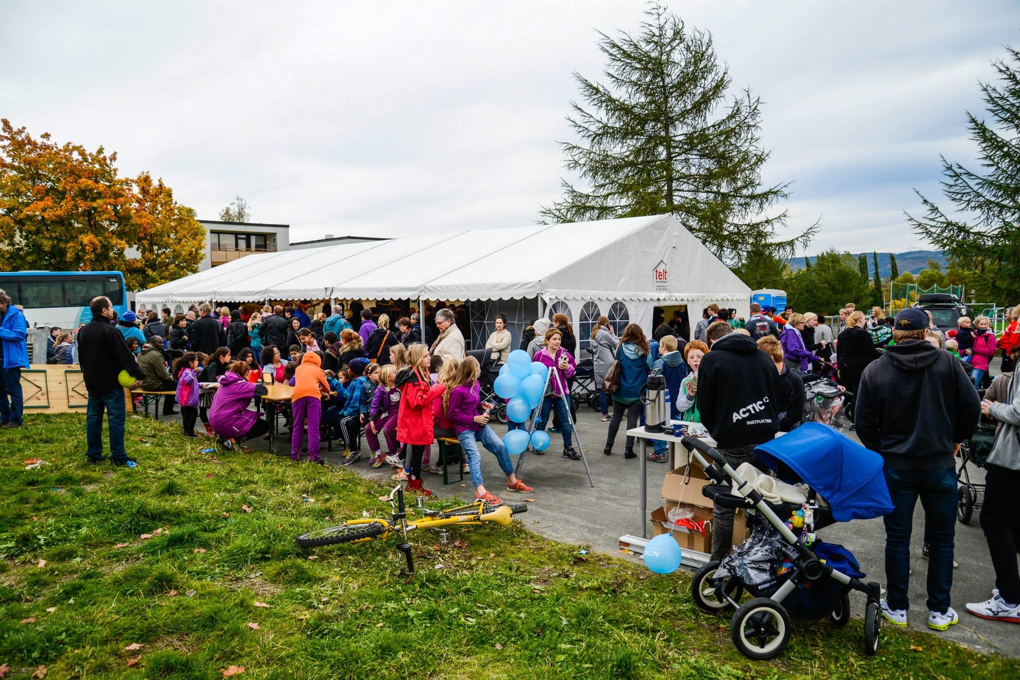 Masse familier er samlet i og rundt et stort partytelt. Barnevogn i forgrunnen.