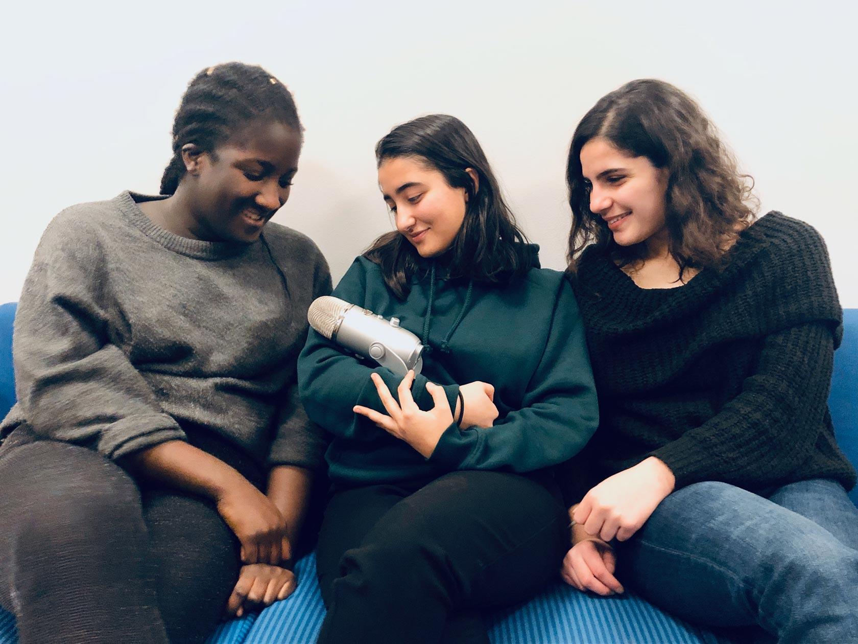 Ei jente ca 15 år holder en stor mikrofon i favnen som en baby. To andre jenter ca 15 år ser beundrende på.