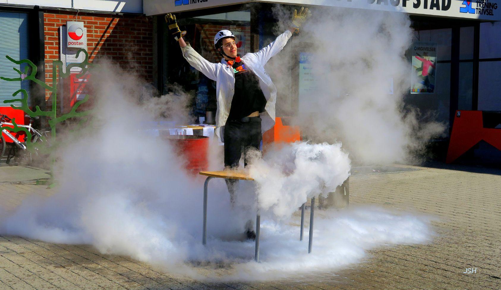 Mann i frakk med hjelm og beskyttelsesbriller står midt på torget i ei røyksky og slår ut med armene