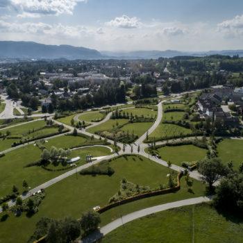 Dronebilde av stort parkanlegg med geometriske gangveier i sol