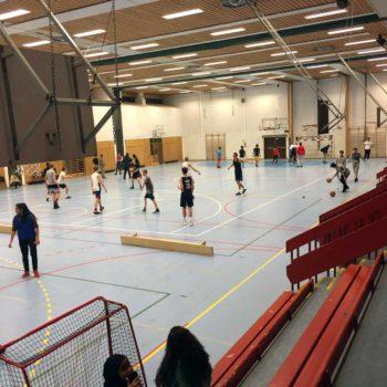 Ulike grupper holder på med forskjellige sportsaktiviteter i en idrettshall