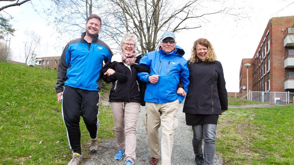 Fire glade personer går tur arm i arm i et urbant grøntområde