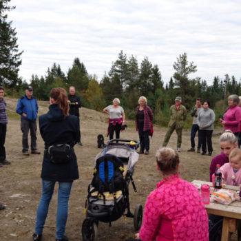 Ca. 20 personer, voksne og barn, står i en sirkel på en åpen plass i skogen
