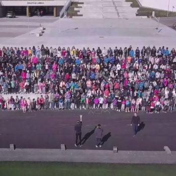 Dronefoto av en hel barneskole som er samlet i et amfi.