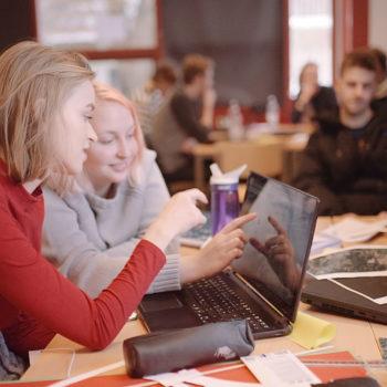To jenter ca. 16 år sitter i et klasserom. Gruppearbeid pågår. De snakker om noe de ser på en dataskjerm.