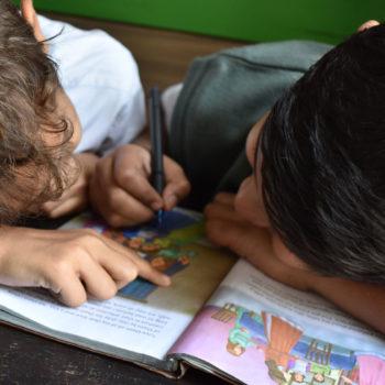 To gutter ca. 7 år lener seg sammen over ei arbeidsbok.
