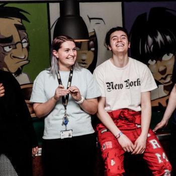 To ungdommer i hijab og russebukse ler sammen med to voksne miljøarbeidere på en ungdomsklubb