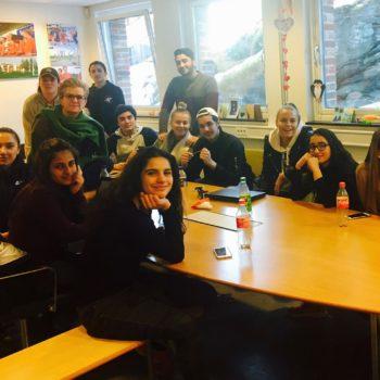 Blide ungdommer er samlet rundt et møtebor