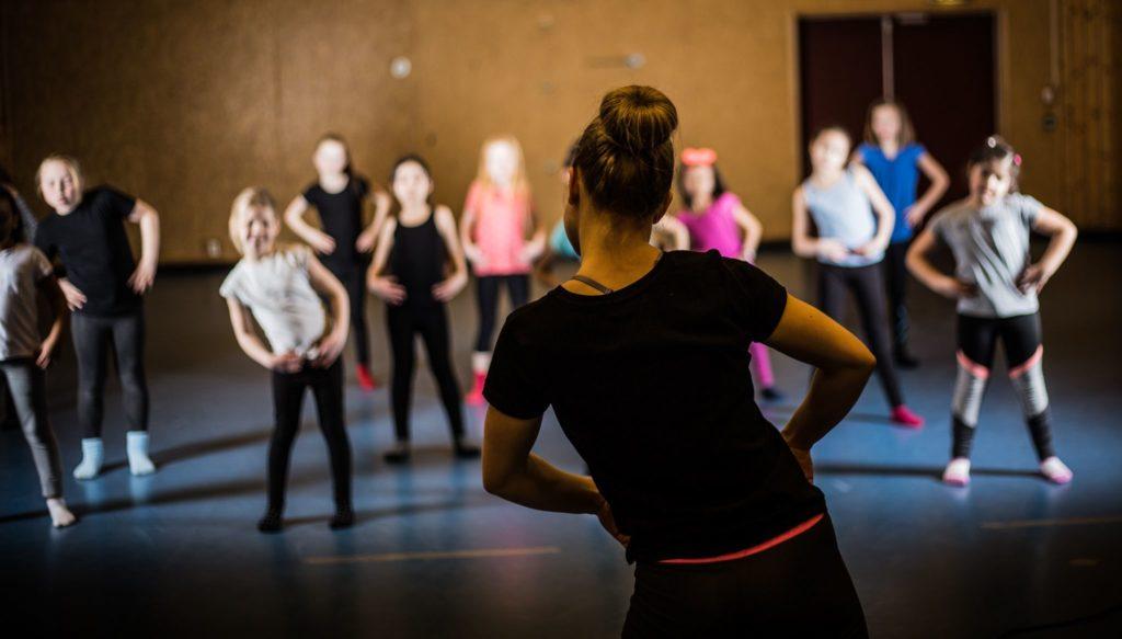 Dame med ryggen til instruerer barn og ungdommer i dans.