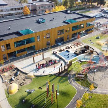 Dronebilde av den nye barnehagen med uterom.