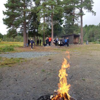 Uteaktiviteter i skogsterreng, bål i forgrunnen
