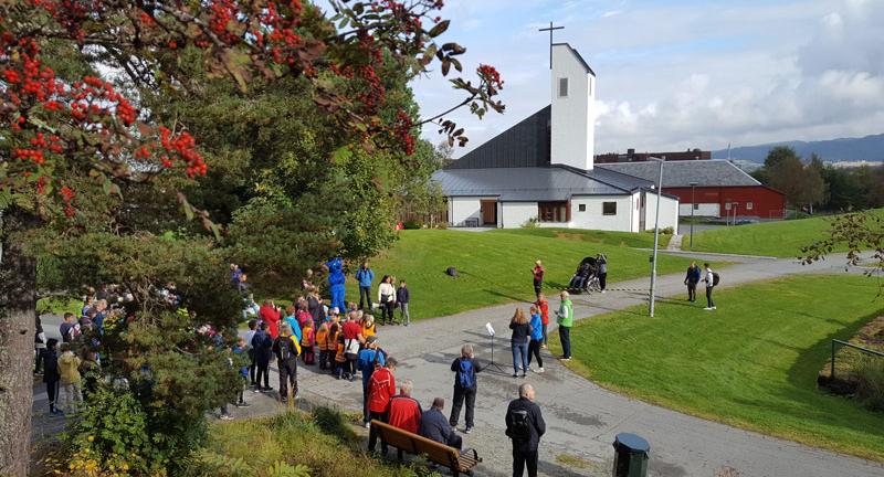 Folk i turklær er samlet i utkanten av et grøntområde. Kirka i bakgrunnen