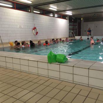 Barn ca. 5 år og foreldre oppstilt på rekke i bassenget
