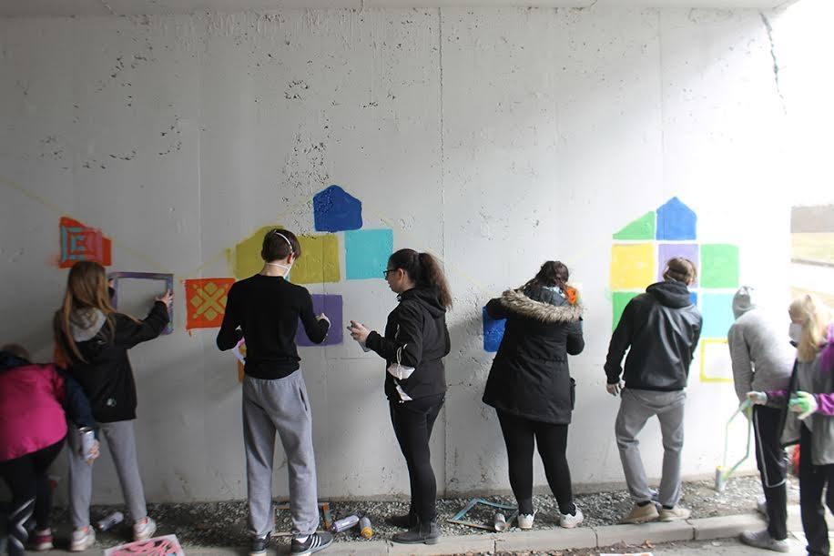 Ungdommer maler fargerike mønstre på en grå murvegg i en fotgjengerundergang.